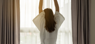 Woman stretching her arms above her head in front of a window in a white robe.