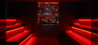 Lava Sauna, red lit wooden beaches with a glowing coal wall decor.
