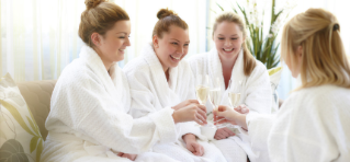 Four women clinking glasses of fizz in white robes sitting on comfortable sofas.
