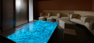 Meditation room with padded seating facing a relaxing water feature.