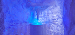 Blue lit ice cave with icicles coming from the ceiling funnelling ice into a pillar.