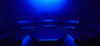 Blue lit steam room with sparkling black tiles and bench seating.