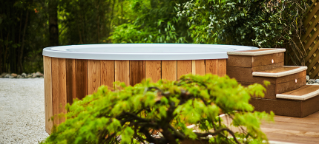 Wooden covered hot tub surrounded by a cosy woodland environment.
