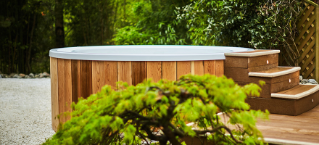 Wooden panelled hot tub outside in a forest area.
