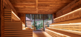 Nordic sauna with lit wooden benches looking out on beautiful forests.