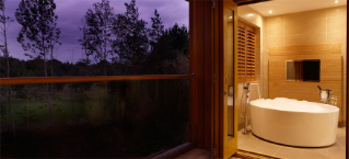 Purple skied woodland landscape looking into a bathroom with a large circular bath tub.